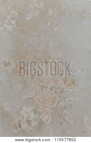 A Macro Photo Of A Detailed White Wedding Dress With White Flowers And Fake Diamonds Knitted To The