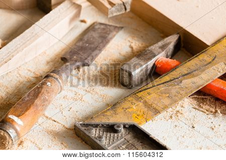 Hammer, chisel and angle carpenter lie on a workbench among scraps of wood