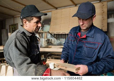 Supervisor and worker to discuss the details of the production of wooden furniture.