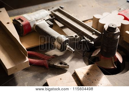 Carpentry tools - gun nailing and pliers lie on a workbench