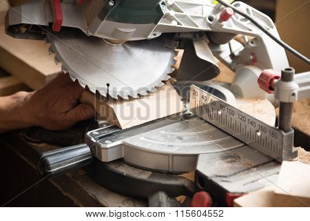 Carpenter working on sawing a board machine with a circulation saw