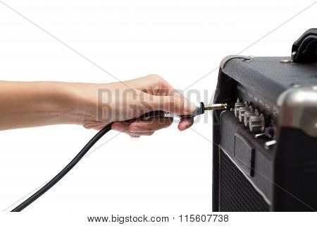Woman Hand Plugging Into The Amplifier Guitar On White Background