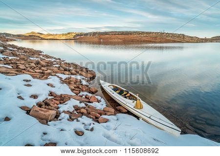 decked expedition canoe on a shore  of Horsetooth Reservoir near Fort Collins in northern Colorado, winter scenery with some snow