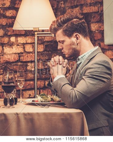 Stylish wealthy man pray before meal at restaurant.