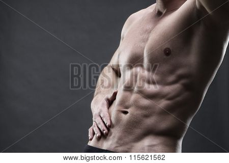 Handsome Muscular Bodybuilder Posing On Gray Background. Low Key Studio Shot With Copy Space