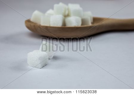 Sugar Cubes on Spoon on Isolated White Background with Harsh Shadow which can be used to imply dark side of Sugar