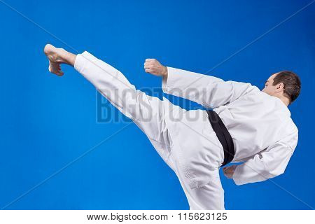 On a light background athlete beats kicking