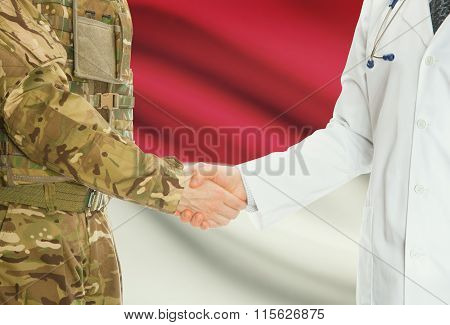 Military Man In Uniform And Doctor Shaking Hands With National Flag On Background - Monaco