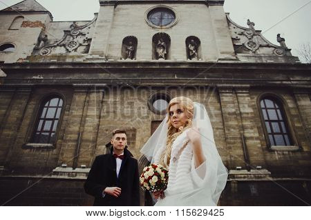 Gorgeous newlywed bride in white coat and handsome groom valentynes posing in front of old baroque church poster