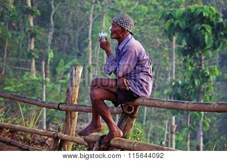 Old local indonesian man smoking in Java