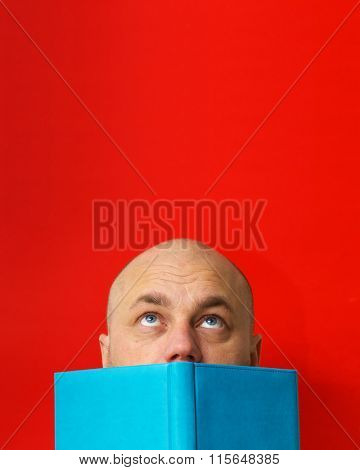 Man covered his face with a book.  Lookup. Red background.