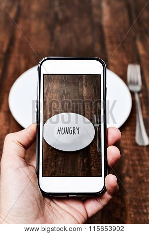 closeup of a young caucasian man taking a picture with his smartphone of a plate with the word hungry written in it, placed on a wooden table