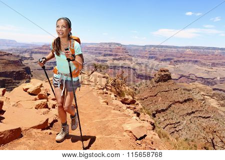 Smiling young female hiker walking on Grand Canyon. Full length of beautiful woman holding hiking poles while climbing rocky mountains. Attractive trekker is enjoying vacation.