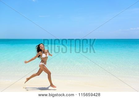 Carefree young woman with arms outstretched jumping on sea shore during summer. Full length of exhilarated female in white bikini. Tourist is enjoying vacation during summer.
