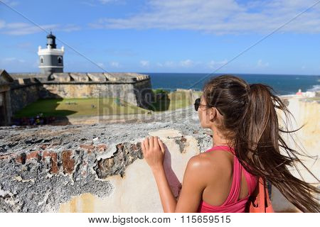 Puerto Rico travel tourist woman in San Juan, looking down at the fort Castillo San Felipe Del Morro, famous attraction of Old San Juan city in Puerto Rico, USA. Summer holidays.
