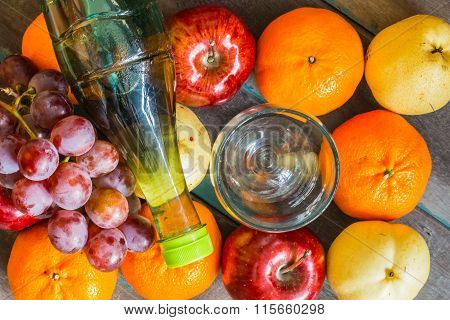 Bottle of juice placed on many types of fruits.
