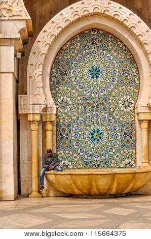 CASABLANCA, MOROCCO, APRIL 2, 2015: Local man rests on the fountain of Hassan II Mosque or Grande Mosquee Hassan II