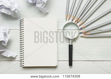 crumpled paper balls, magnifying glass, pencils and notebook with blank white sheet  on wooden table