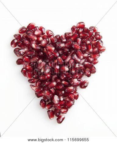 ripe pomegranate seed heart shape isolated white
