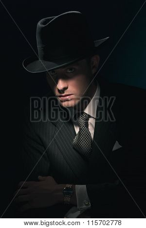 Retro Mysterious Gangster With Hat In Suit And Tie. Against Dark Blue Wall.