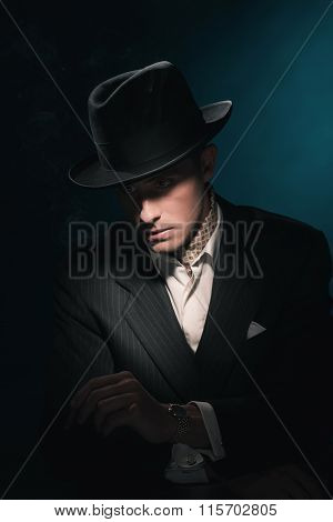 Cigar Smoking Retro Gangster With Hat In Suit. Dark Blue Background.