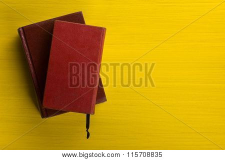 Stack of hardback books, diary on wooden deck table and yellow background. Back to school. Copy Spac