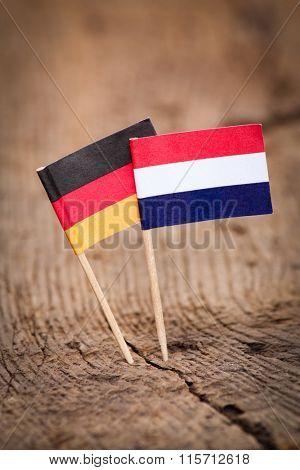 Flags of Germany and Netherlands on wooden background