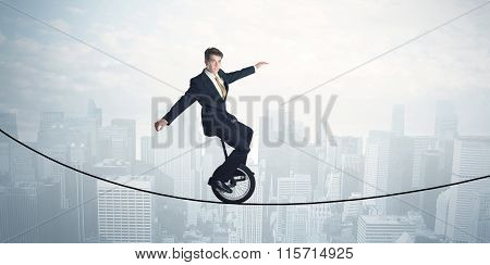 Brave guy riding a monocycle on a rope above cityscape concept