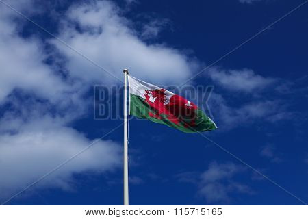 Welsh flag flies against blue sky