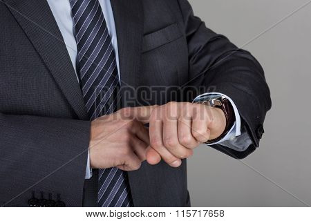 Business Man Looks At His Wrist Watch Checking The Time