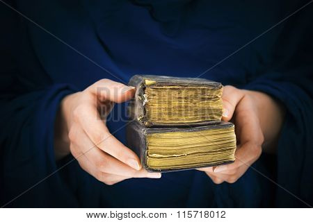 Woman's Hands Holding Two Old Books