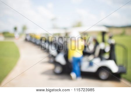 Abstract Blurred Photo Of Golf Cart And Caddy In Uniform With Beautiful Nature Green.