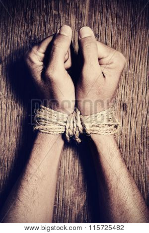 high-angle shot of the hands of a young man tied with rope on a rustic wooden table, as a symbol of oppression or repression, with a dramatic effect