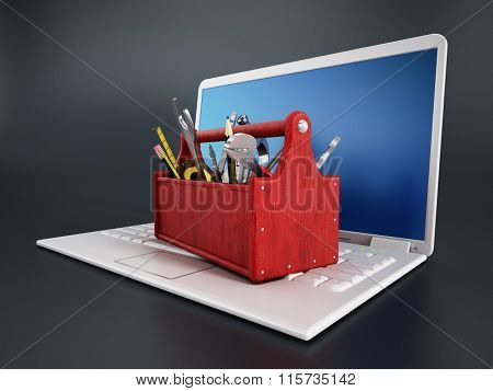 Red toolbox standing on laptop computer isolated on black background