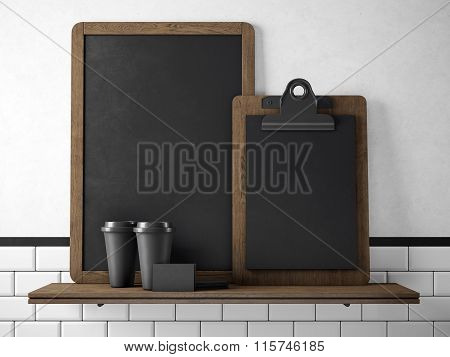 Black chalkboard on bookshelf with two blank coffee cups, businesscards and empty desk. 3d rendering
