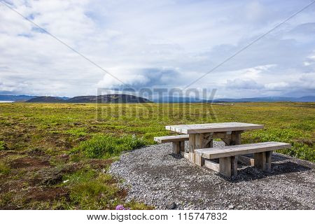 Wooden picknick bench in green landscape. Iceland