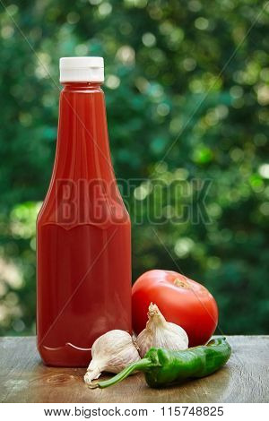 Tomato, garlic, hot pepper and bottle of ketchup.