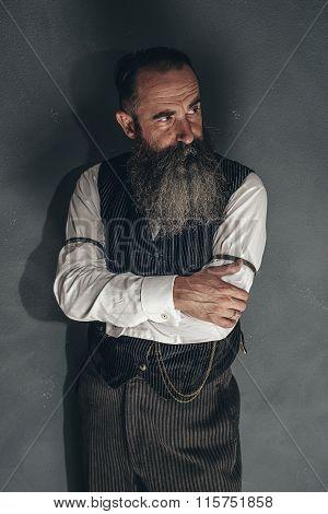 Vintage Beard Man In 1900 Style Fashion Against Grey Wall.