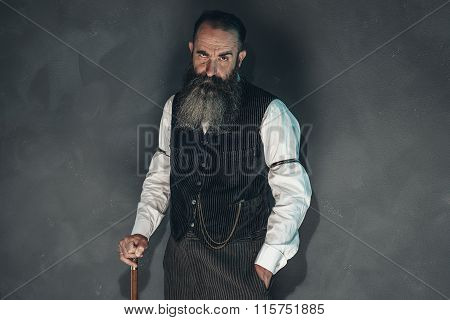 Vintage Beard Man In 1900 Style Fashion With Cane Against Grey Wall.