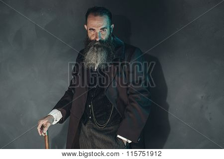 Mysterious Vintage Bearded Man In 1900 Style Fashion With Cane Against Grey Wall.