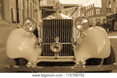 Antique Rolls Royce Car Decorated For Use In A Wedding Event  with passers-by in the background
