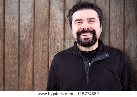 Smiling Bearded Man Against Wooden Wall