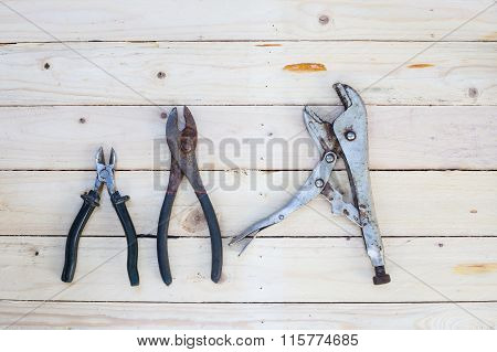 Locking Pliers On White Wooden Floor