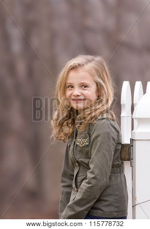 artistic outdoor portrait of a cute blond girl holding on to a fence