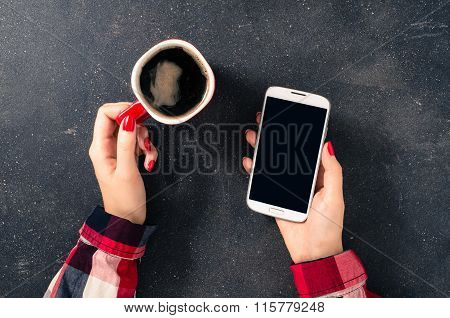 Female hands holding coffee cup and white mobile phone over dark table