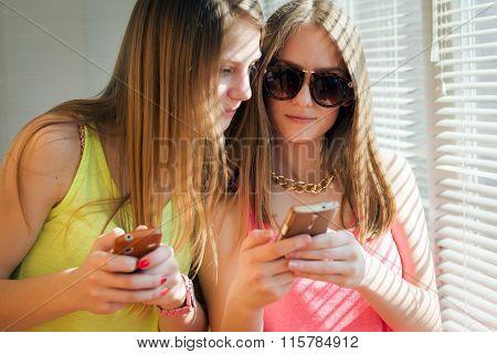 Two teenage girls looking in their gadgets