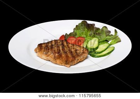 Photo Of A Pork Stake On A White Plate With A Cucumber, Tomato And A Lettuce Leaf