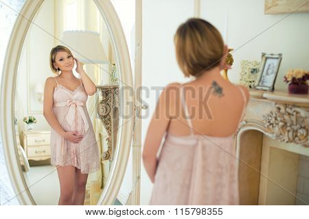 Beautiful Slim Pregnant Girl With A Tattoo On Shoulder Blade Looking At Herself In The Mirror