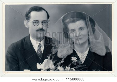 A vintage photo shows wedding portrait of newly-weds.