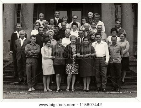 Vintage photo shows group of people in front of building circa 1970s.